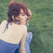 Red haired girl sitting on fresh grass — Stock Photo #36719467