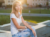 Blond against sun sitting on parapet in park — Stock Photo