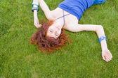 Redhead girl lying on fresh grass — Stock Photo