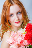 Redhead with bunch of flowers in studio on white — Stock Photo