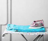 Pile of towels and smoothing-iron on the table — Stock Photo