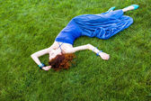 Smiling redhead girl on green grass — Stock Photo