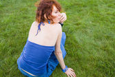 Red haired girl sitting on fresh grass — Stock Photo