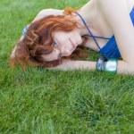 Beautiful redhead girl lying on green grass — Stock Photo