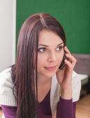 Brunette indoor call by cell phone — Stock Photo