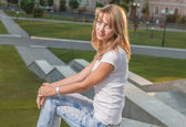 Blonde sitting on parapet — Stock Photo