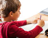 Boy writing indoors — Stock Photo