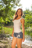 Beautiful young blonde woman in white tank top and denim shorts laughing out loud (LOL) outdoors — ストック写真