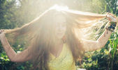 Portrait of happy woman with hand in hair against nature — Stock Photo