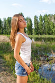 Calm woman against lake and forest — Stock Photo