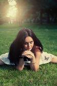 Brunett liggande på grönt gräs — Stockfoto