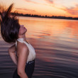 Beautiful brunette shaking her long black hair near water — Stock Photo #45614477