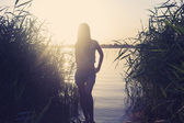Silhouette of a  female against water — Stok fotoğraf