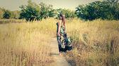 Woman walk in a high grass in dress — Stock Photo