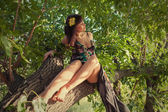 Sensual girl sitting on a tree outdoors — Stok fotoğraf
