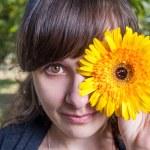 Cute girl hide her eyes by gerbera flowers — Stock Photo #48098911