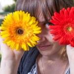 Cute girl hide her eyes by gerbera flowers — Stock Photo #48099349