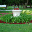 Big vase in a center of flowerbed — Stock Photo #48099427