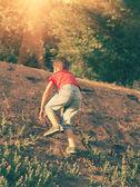 Boy climbing up the slope backlit — Stock Photo