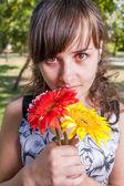 Brunett med blommor i händerna — Stockfoto