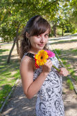 Brunette with flowers in her hands — Stok fotoğraf