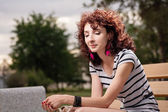 A beautiful girl is sitting on a park bench — Stock Photo