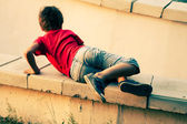 Boy playing on a cemet parapet — Stock Photo