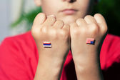 Flag of Russia and Unite States on fist of a boy — Stock Photo