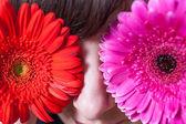 Cute girl hide her eyes by gerbera flowers — Stock Photo