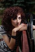 Krásná dívka sedí na lavičce v parku — Stock fotografie