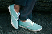 Azure sneakers on woman feet — Stock Photo