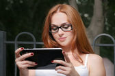 Young redhead woman with a tablet-pc — Stockfoto