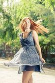 Young pretty woman dancing in city park — Foto de Stock