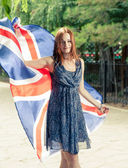 Cute  girl against  holds britain flag — Stock Photo