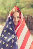 Smiling girl covered with US flag — Stock Photo