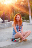 Red haired young women sitting on skateboard with her legs crossed backlit by sun — Stock Photo