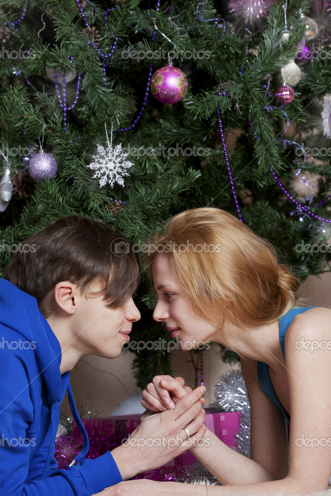 Young couple celebrates Christmas near a fir tree — Stock Photo #13205710