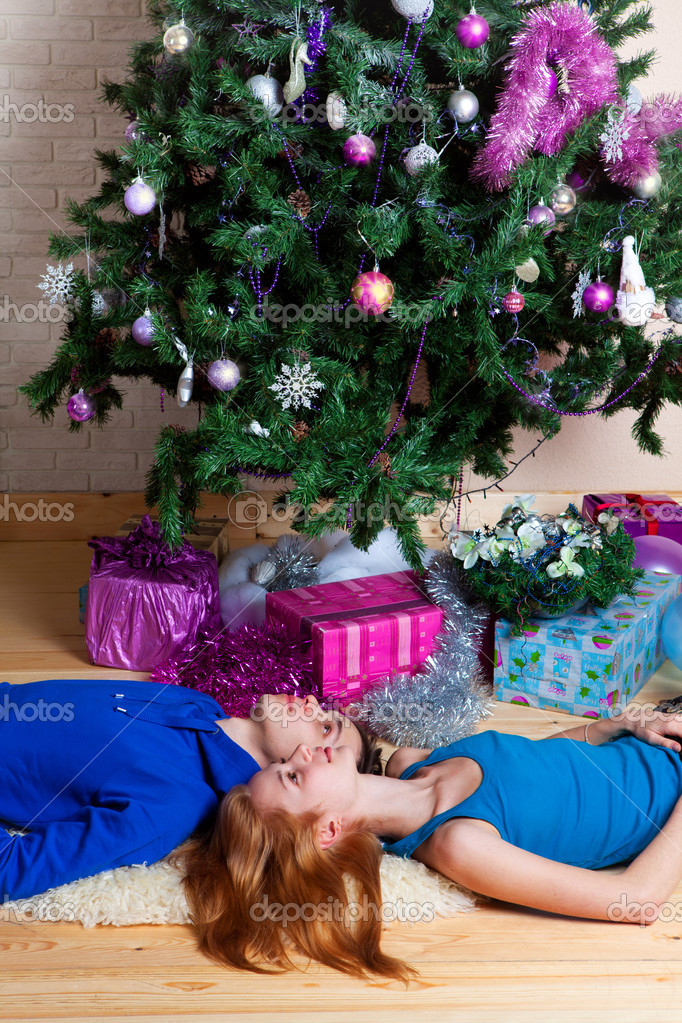 Young couple celebrates Christmas near a fir tree  Stock Photo #13205724