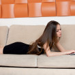 Young woman with a computer on the sofa — Stock Photo