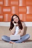 Young woman with a computer and phone — Stock Photo