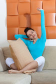 Woman sitting on a sofa with a pillow — Stock Photo