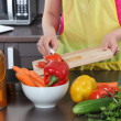 Woman in the kitchen cut vegetables — Stock Photo #26861875