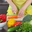 Stock Photo: Woman in the kitchen cut vegetables