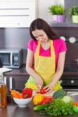 Femme dans la cuisine des légumes coupés — Photo