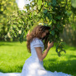 Woman in white dress in apple orchard — Stock Photo