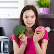 Woman chooses what to eat vegetables or a cake — Stock Photo #37428269