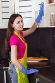 Beautiful brunette cleans the kitchen furniture — Stock Photo