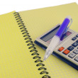 Calculator and pen on the yellow writing-book — Stock Photo