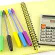 Old calculator and color pens on the yellow writing-book — Stock Photo #14725645
