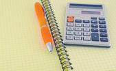 Digital calculator and orange pen on the yellow writing-book — Stock Photo